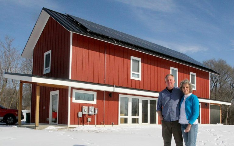 Matt and Tracee Vetting stand in front of their net-zero energy passive house built in Rochester, Minnesota