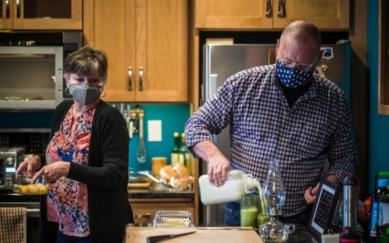 Mary and Ivan Idso cooking dinner while using energy from their solar powered battery